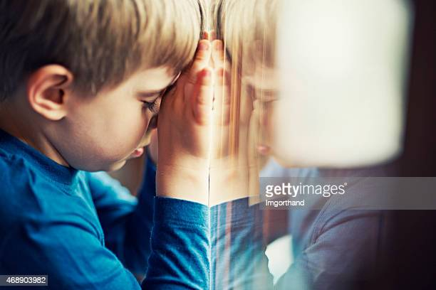 sad little boy leaning aganing the window - orphan stock pictures, royalty-free photos & images