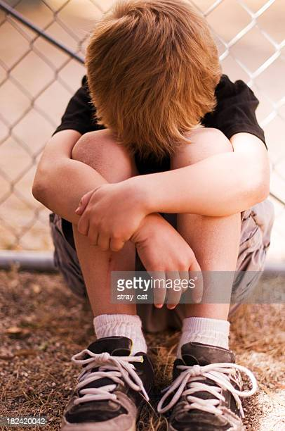 Sad little boy resting his head in his lap in front of fence