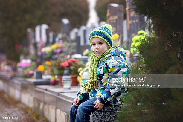 Sad little boy, sitting on a grave in a cemetery, feeling sad and crying