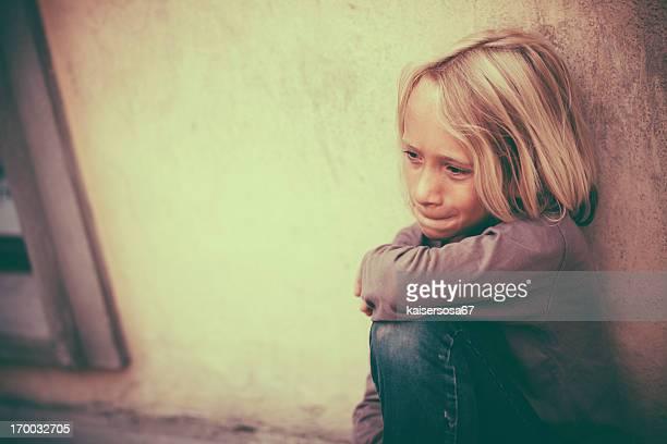 Sad little boy sitting on sidewalk