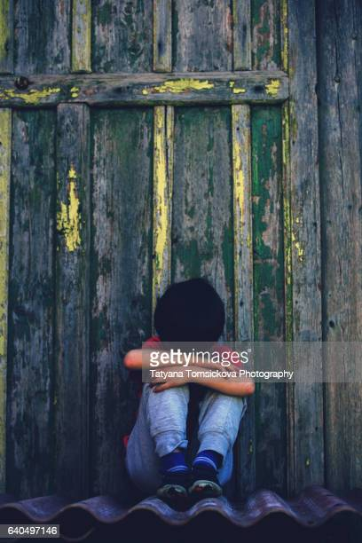 sad little child, sitting in front of old wooden door, crying alone - losing virginity stock pictures, royalty-free photos & images