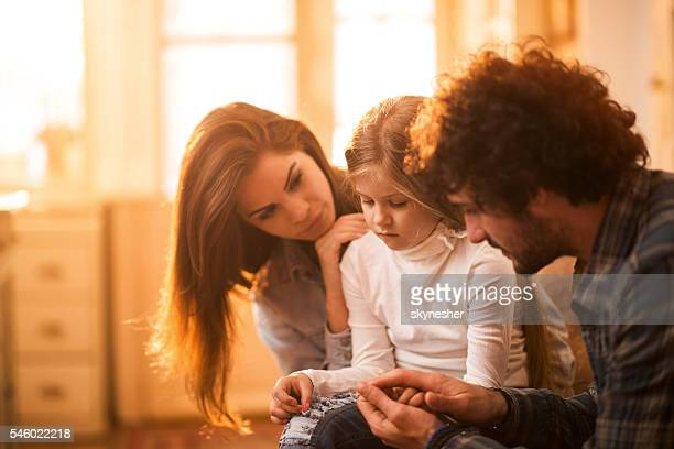 sad little girl at home being consoled by her parents. - consoling stock pictures, royalty-free photos & images