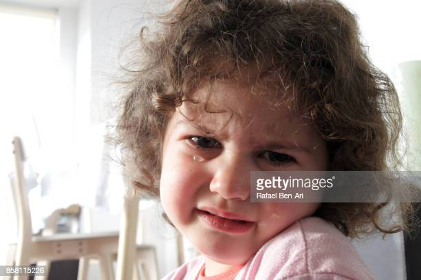 Sad little girl cries at home