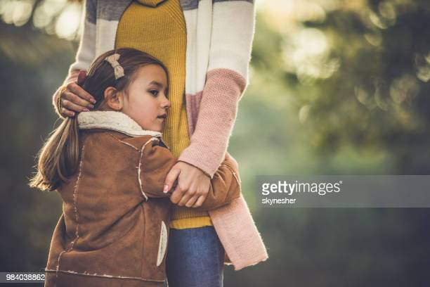 sad little girl embracing her mother in nature. - sad mom stock pictures, royalty-free photos & images