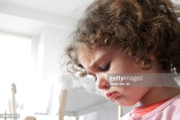 Sad little girl has a tear on her cheek