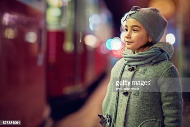 Trauriges Mädchen steht an der Tram-Station in der Nacht