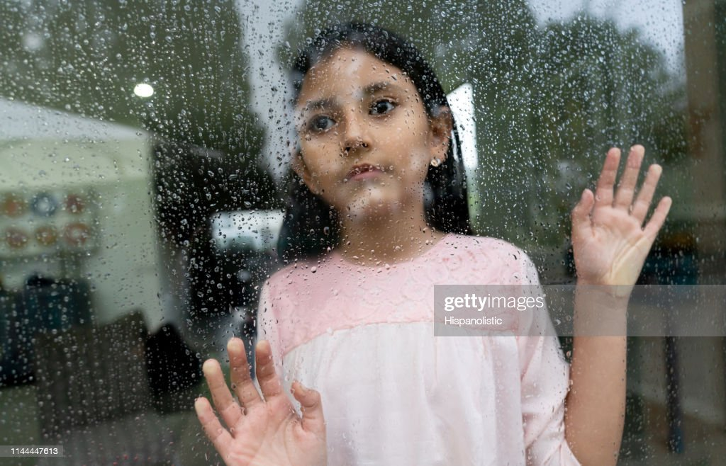 Sad little girl looking out the window on a rainy day looking pensive : Stock Photo