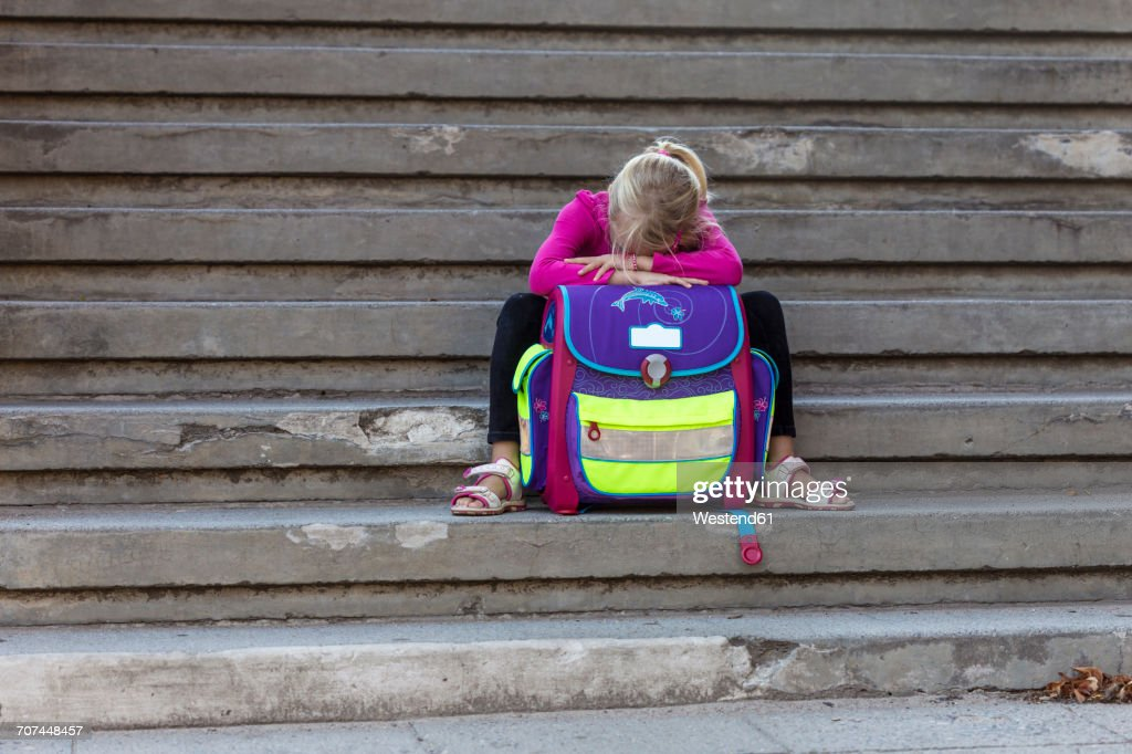Sad little girl sitting on stairs with school bag : Stock Photo