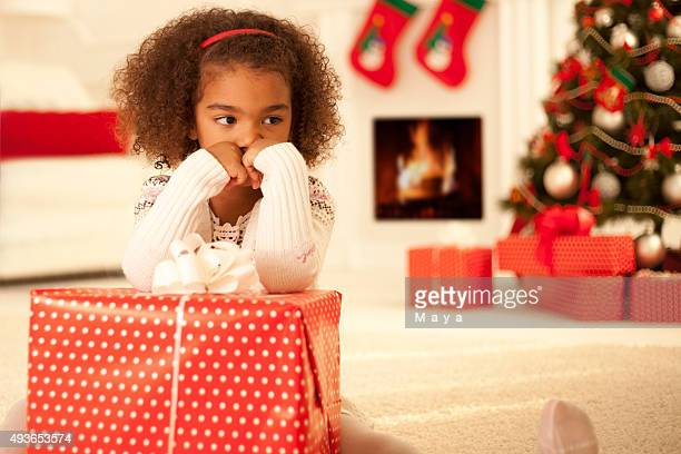 Sad little girl with Christmas present