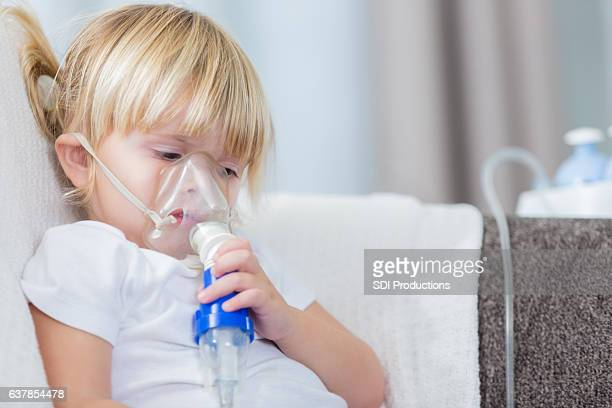 Sad little girl with cystic fibrosis receives breathing treatment