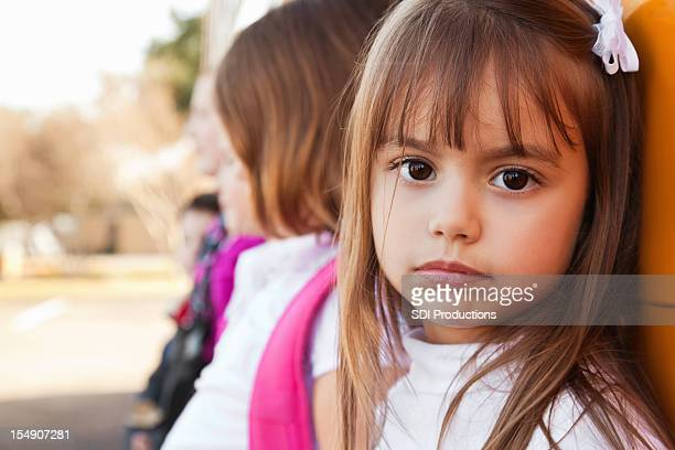 Sad Little Girl With Other Students at School Bus
