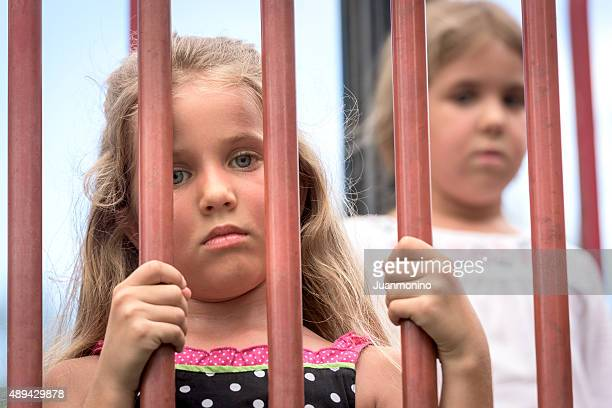 sad little girls in a cage - child behind bars stock pictures, royalty-free photos & images