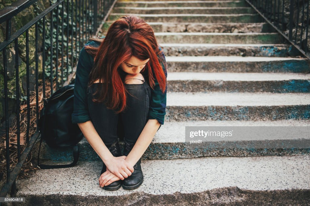 Sad lonely girl sitting on stairs : Stock Photo