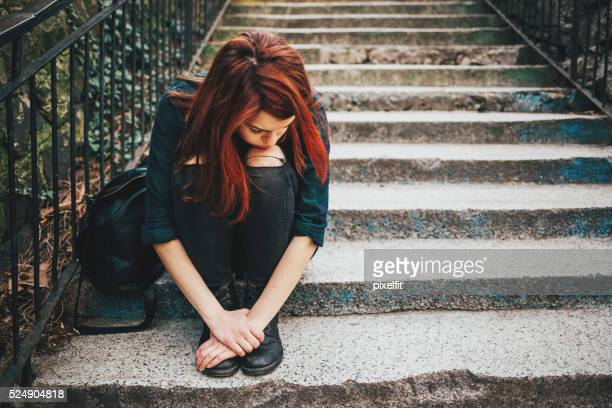 sad lonely girl sitting on stairs - tienermeisjes stockfoto's en -beelden