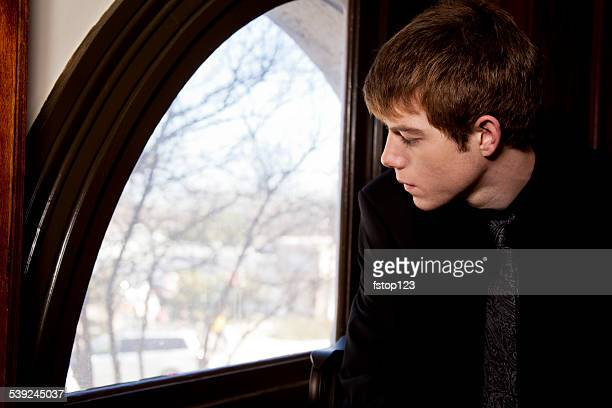 sad, lonely teenage boy looking out window. funeral, loss, grief. - funeral photos stock photos and pictures