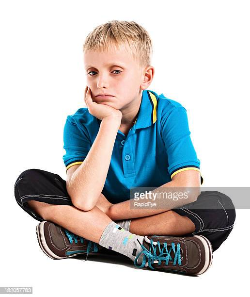Sad looking 9 year old boy seems withdrawn and unhappy.