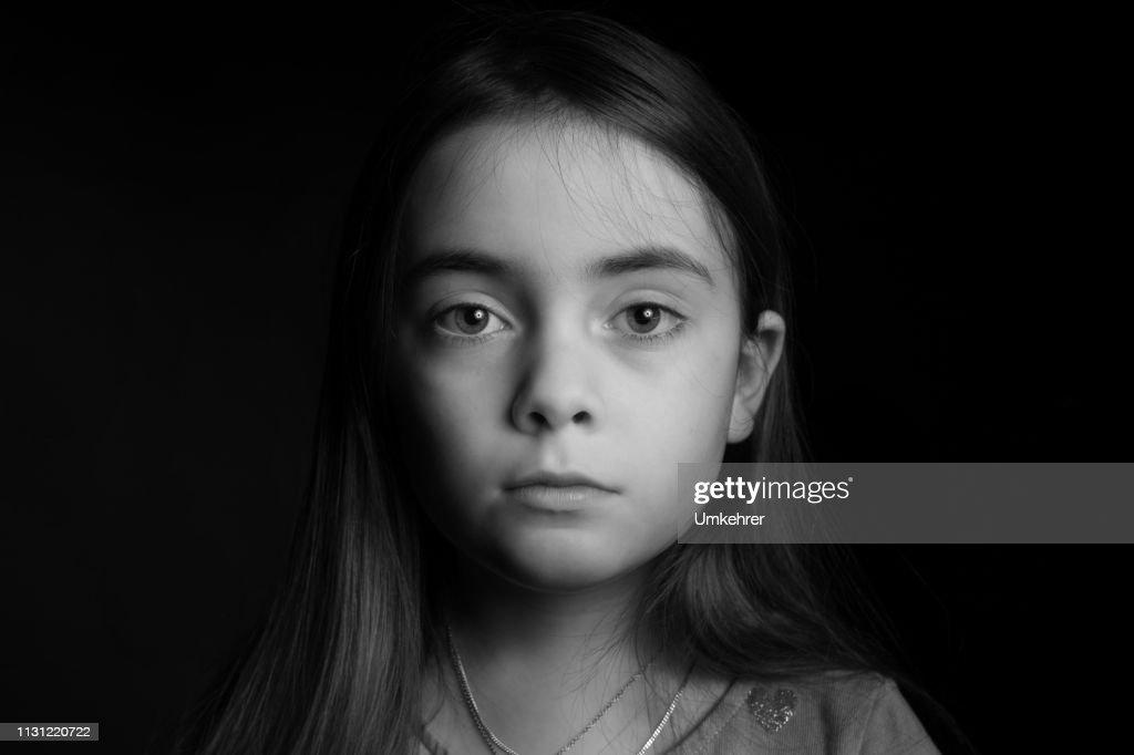 黒の背景の前で悲しい探している女の子 : ストックフォト