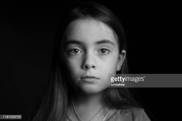 sad looking girl in front of black background - solo una bambina femmina foto e immagini stock
