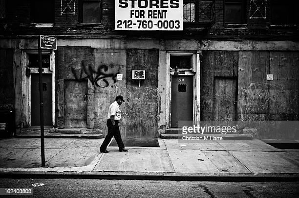 Sad looking man, random pedestrian walking by boarded up and graffiti covered store fronts on 9th Ave, Hell's Kitchen, Manhattan, NYC