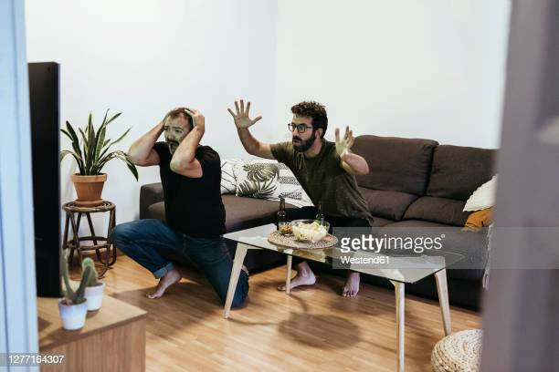 sad male friends watching sports over tv in living room seen through doorway - match sport stock pictures, royalty-free photos & images