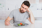 Sad man diet ready to eat salad for weight loss