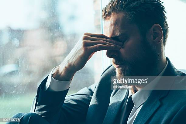 Sad man looks depressed and covers his eyes
