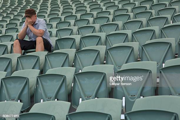 Sad man sitting alone in empty stadium