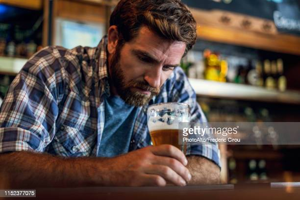 sad man sitting in beer bar - beer alcohol stock pictures, royalty-free photos & images