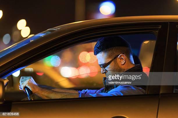Sad man sitting in car at night