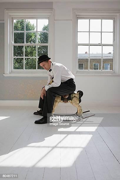 Homme triste assis sur un cheval à bascule