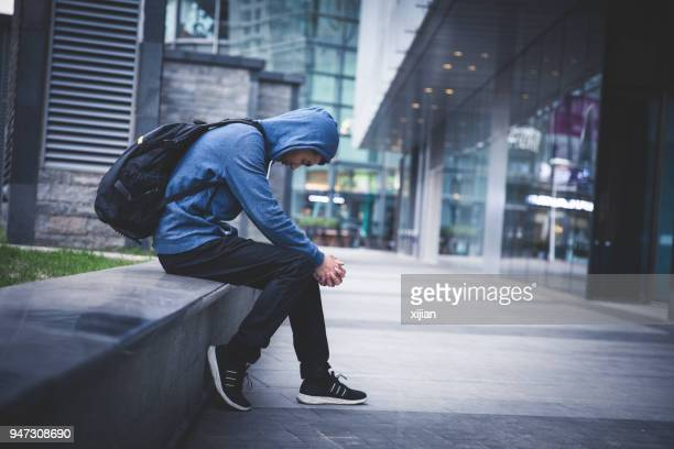 sad man sitting on city street - addict stock photos and pictures
