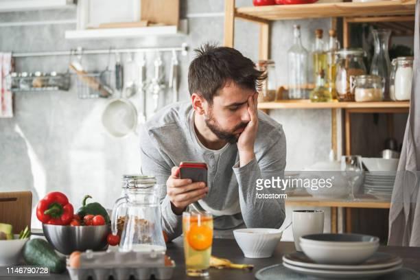 hombre triste usando teléfono inteligente durante el desayuno en casa - manos a la cabeza fotografías e imágenes de stock
