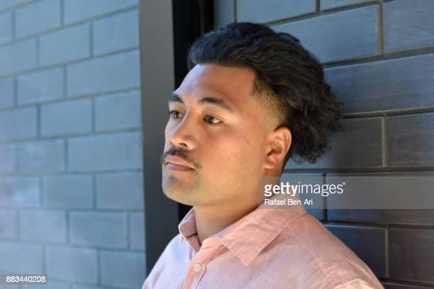 Sad Maori man leans against brick wall