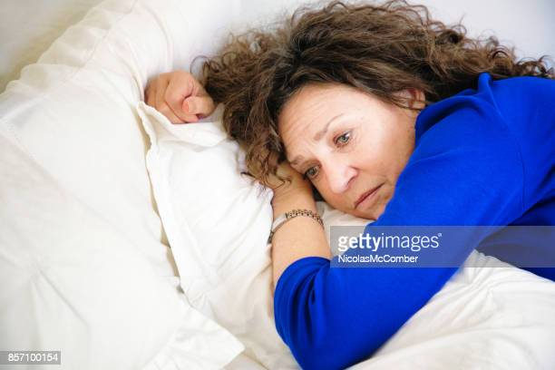 Sad Mature Caucasian female lying down on bed pensive