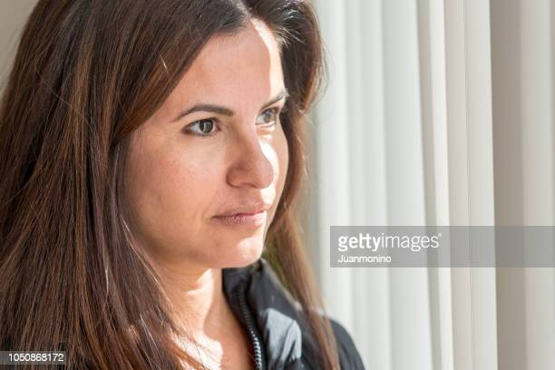 sad mature woman looking through a window - menopause stock photos and pictures