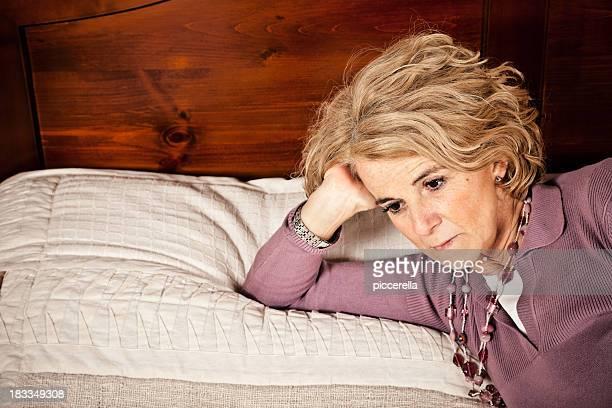 悲しげな成熟した女性のベッドに横たわる