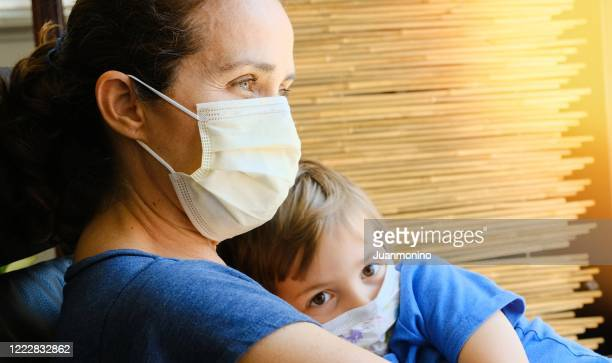 sad mature woman posing sitting embracing her son both wearing protective masks - illness prevention stock pictures, royalty-free photos & images