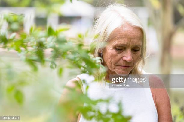Sad mature woman walking in the park, copy space