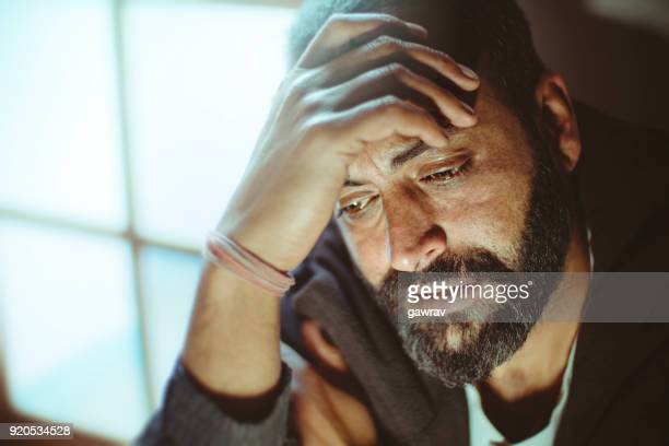 sad mid adult man thinking at home. - mid adult men stock pictures, royalty-free photos & images