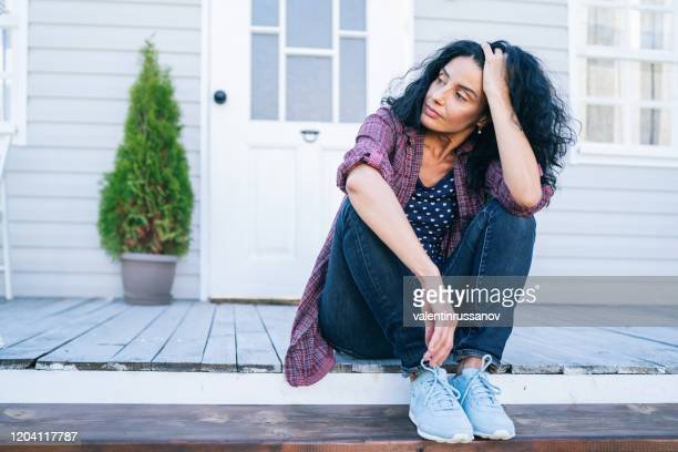 sad mid adult woman sitting on stairs in front of her house - menopause stock pictures, royalty-free photos & images