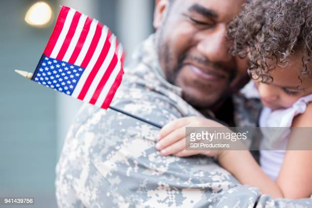 sad military soldier says goodbye to his little girl - military flags stock photos and pictures