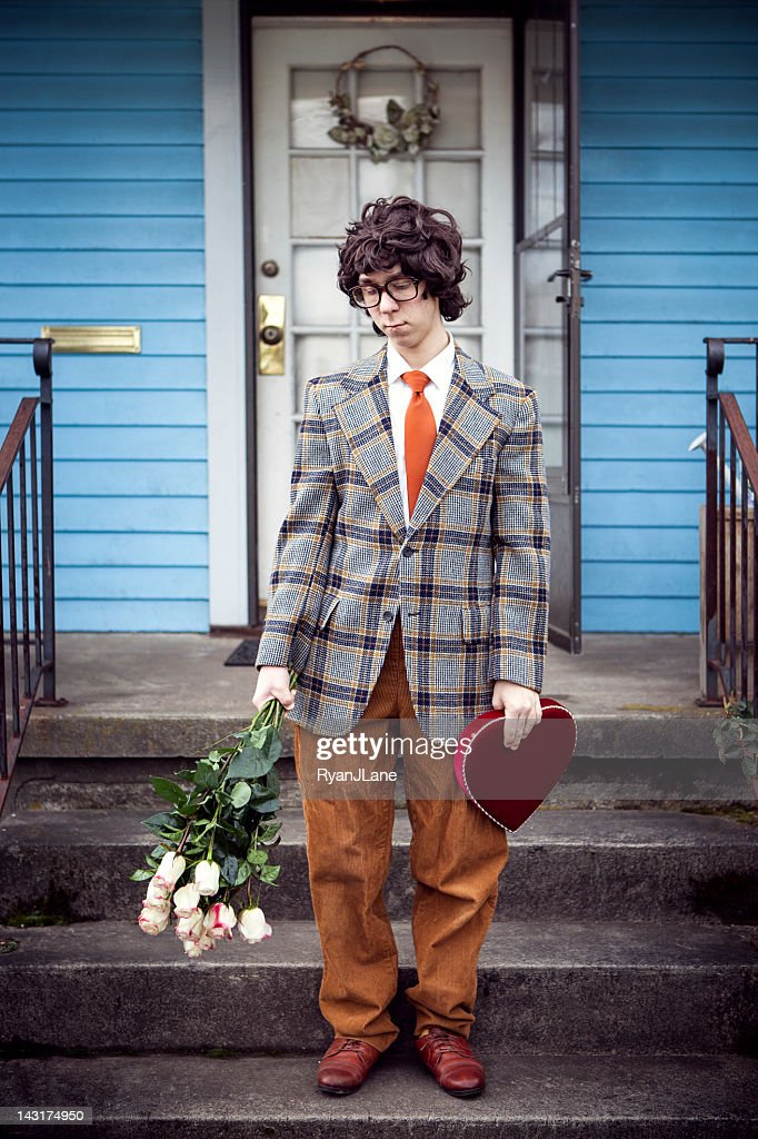 Sad Nerd With Valentine Gift And Flowers On Front Porch Stock Photo