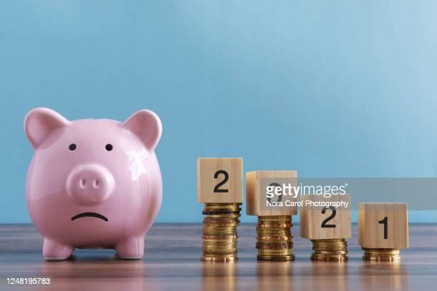 sad piggy bank and stack of coins 2021 - zinssatz stock-fotos und bilder