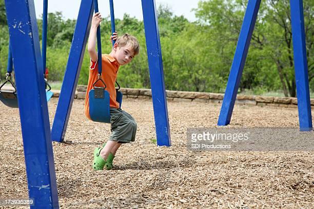 sad preschool boy swinging at the playground with copy space - uitsluiting stockfoto's en -beelden
