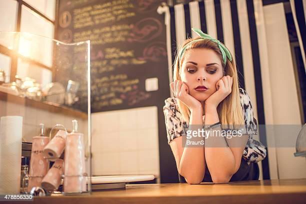 Sad retro styled female worker waiting for her customers.