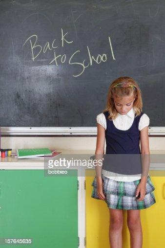 Sad School Girl In Uniform And Classroom Setting Stock
