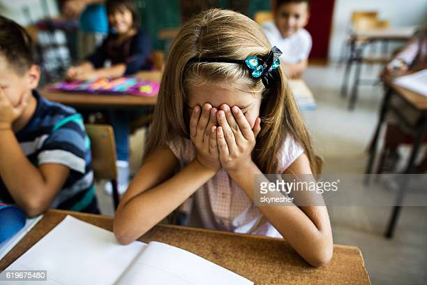 Sad schoolgirl holding her head in hands in the classroom.