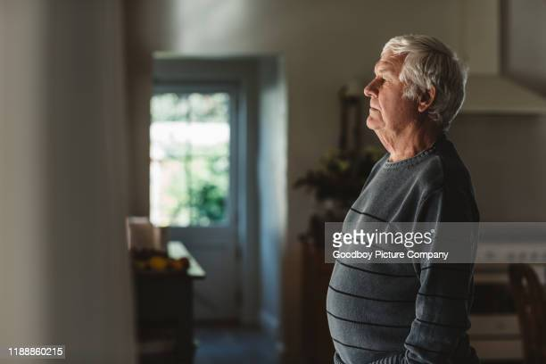 sad senior man looking out through a window at home - mourning stock pictures, royalty-free photos & images