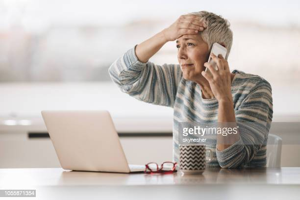 sad senior woman having problems while talking on cell phone. - distraught stock pictures, royalty-free photos & images
