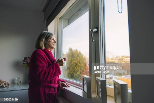 sad senior woman looking out of the window - looking through window stock pictures, royalty-free photos & images